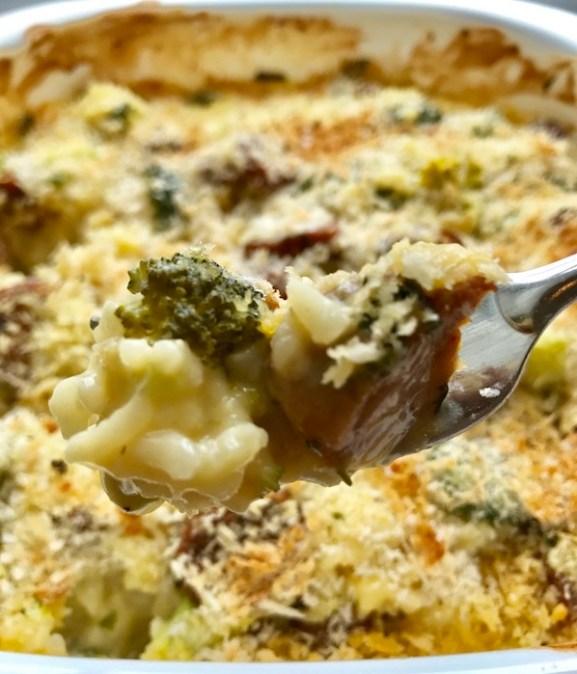 Cheesy Chicken Sausage & Broccoli Rice Casserole bite on fork above casserole dish.