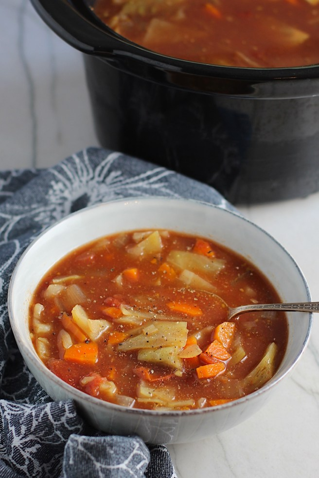 Detox Cabbage Soup in a bowl with spoon on blue napkin on counter with slow cooker in background. The soup is tomato-based with chunky veggies: cabbage, tomato, carrots, onion, and garlic.