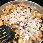 Cauliflower and mushrooms cooking in skillet with flour added for this Creamy Cajun Cauliflower and Beans Recipe served over Quinoa.
