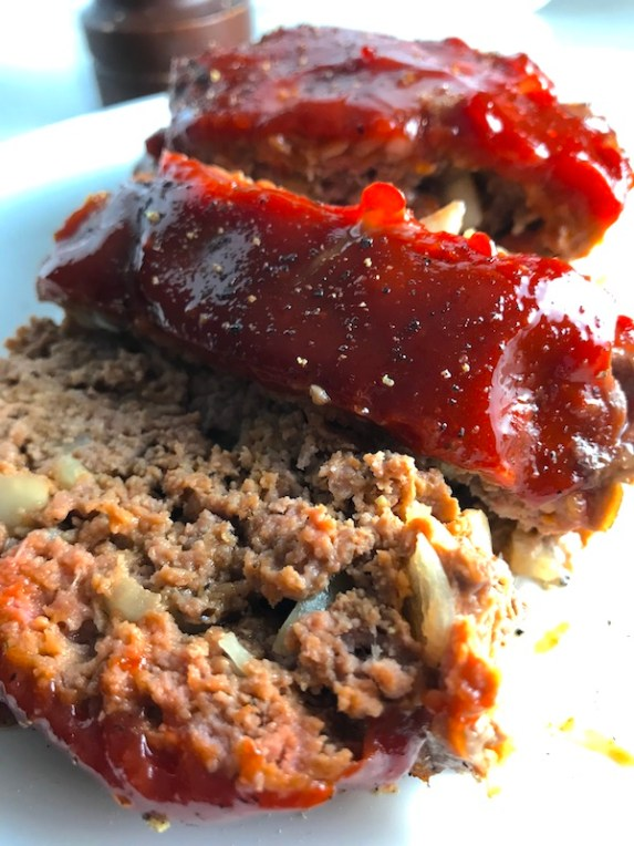 Close up picture of sliced meatloaf with ketchup on top. This 5-Ingredient Easy Meatloaf recipe may be short on ingredients, but it is loaded with flavor. The lack of breadcrumbs means you don't have them soaking up the juices, so the meat stays moist - and it's gluten free too! Parmesan cheese, onion, egg, ketchup, salt, and pepper are all that go into this yummy loaf of goodness!