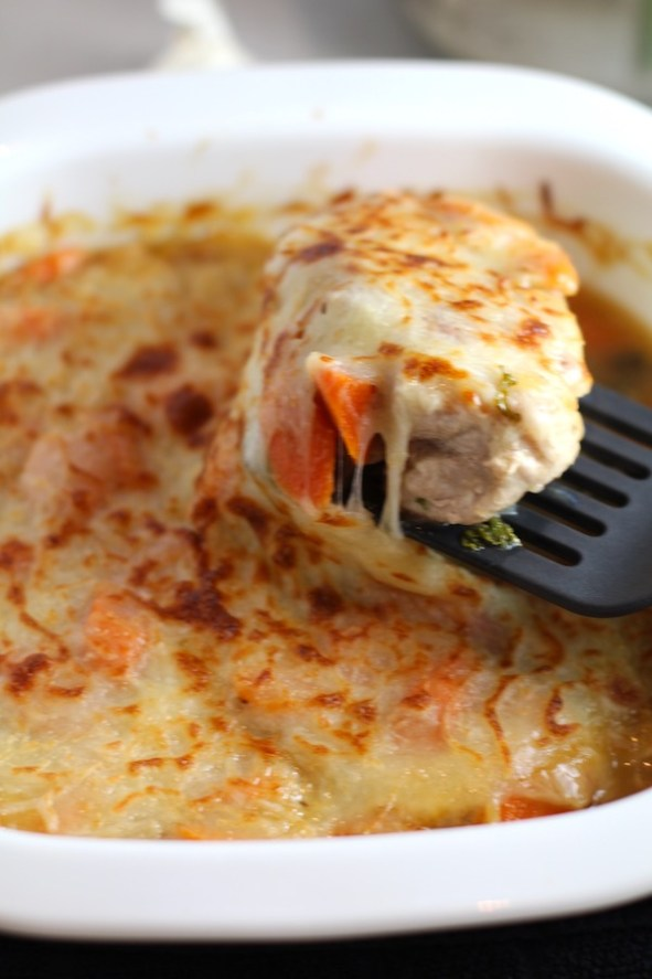 Close up of Smothered Pork Chop Casserole piece being lifted up with spatula. This is a true midwestern comfort dish with layers of vegetables and meaty pork chops smothered in a creamy sauce and cheese.  The pork chops in this delicious casserole are left whole so that you get an entire portion dripping in goodness in one scoop.