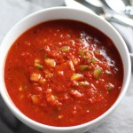 This Roasted Red Pepper Gazpacho recipe is Summer in a bowl - cool, tangy, crunchy, fresh, and creamy. The base is tomato, but this Gazpacho recipe puts Roast Red Pepper in the starring role, which brings another layer of creamy sweetness. Then you get the crunch from the green pepper, cucumber, garlic and scallions.