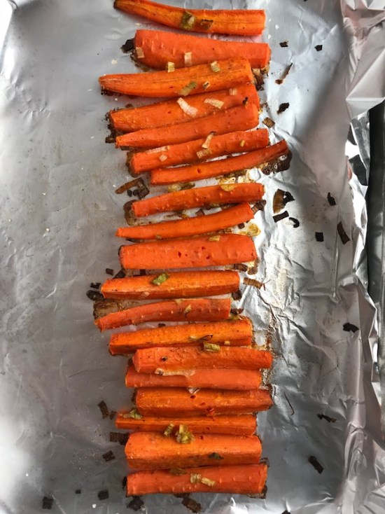 Roasted Carrots on a pan with scallions. Roasted Carrots with smoky cumin and scallions, then topped with Avocado Crema are such a delicious and quick side dish for dinner.  Roasting brings out the natural sugar in the carrots, so they get a sweet caramelization with the salty and smoky flavors. The Avocado crema gives creamy and silky balance.