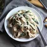 Walnut Sauce mixed with fettuccine and spinach on a plate with a fork. This Walnut Sauce recipe with Ricotta and Spinach is thick, rich, nutty, and creamy.  It's inspired by the traditional Italian Walnut Sauce from the North-Western Italy, Liguria Region, but my Walnut Sauce recipe adds even more decadence with creamy ricotta and more nutty parmesan cheese.