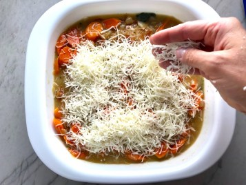 Hand sprinkling shredded mozzarella cheese over carrots, sauce, and pork in casserole dish. Smothered Pork Chop Casserole is a true midwestern comfort dish with layers of vegetables and meaty pork chops smothered in a creamy sauce and cheese.  The pork chops in this delicious casserole are left whole so that you get an entire portion dripping in goodness in one scoop.