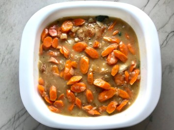 Carrots and sauce on top of pork chops in casserole dish. Smothered Pork Chop Casserole is a true midwestern comfort dish with layers of vegetables and meaty pork chops smothered in a creamy sauce and cheese.  The pork chops in this delicious casserole are left whole so that you get an entire portion dripping in goodness in one scoop.