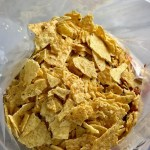 Crushed tortilla chips added to freezer bag for Chipotle Chicken Enchilada Stew. It is one of my Prepped Freezer Meal recipes and it's creamy, cozy, hearty, cheesy, and slightly spicy. All ingredients freeze raw, thaw, then cook in the slow cooker or in the oven. It's a stew because it's thick and hearty with bites of chicken, carrots, onion, chipotle peppers, cumin, garlic and tortilla chips that melt down to thicken this delicious stew.