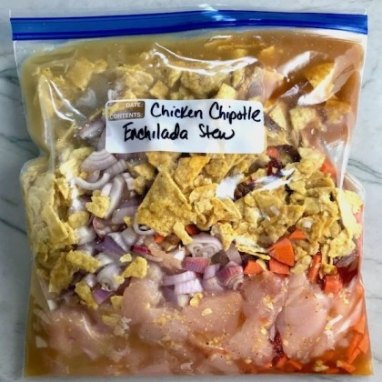All ingredients in a labeled freezer bag for Chipotle Chicken Enchilada Stew. It is one of my Prepped Freezer Meal recipes and it's creamy, cozy, hearty, cheesy, and slightly spicy. All ingredients freeze raw, thaw, then cook in the slow cooker or in the oven. It's a stew because it's thick and hearty with bites of chicken, carrots, onion, chipotle peppers, cumin, garlic and tortilla chips that melt down to thicken this delicious stew.