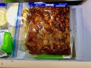 All raw ingredients in freezer bag in freezer for Freezer Hoisin Chicken with Red Peppers, Carrots, Onions, Ginger, and Soy sauce is delicious and so easy to make. You get sweet and savory all in one dish and it's perfect for kids because it's sweet, not spicy at all. Just freeze ahead, thaw, then cook on a sheet pan!