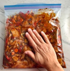 Pressing the Hoisin Chicken ingredients in the freezer bag flat with hand. This Freezer Hoisin Chicken with Red Peppers, Carrots, Onions, Ginger, and Soy sauce is delicious and so easy to make. You get sweet and savory all in one dish and it's perfect for kids because it's sweet, not spicy at all. Just freeze ahead, thaw, then cook on a sheet pan!