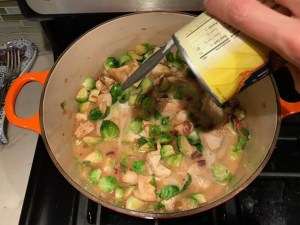 Adding Coconut Milk to brussel sprouts and chicken in pot for the Easy Bacon Brussel Sprouts and Chicken recipe. It's a perfect quick Fall Recipe!  It has a creamy sauce filled with salty bacon, earthy and almost nutty seared brussel sprouts, and hearty healthy chicken. Serve over rice (or Quinoa or pasta!).