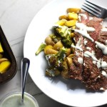 Flank Steak sliced with Potatoes & Broccoli on plate with crema drizzled on top. This is an easy and delicious Sheet Pan Dinner.  The homemade steak rub adds such wonderful flavor. To top this sheet pan dinner, you get this tangy, light Garlic Chive Crema!  Best of all, you only need 1 pan so it's a super easy clean up.  Easy and Delicious!