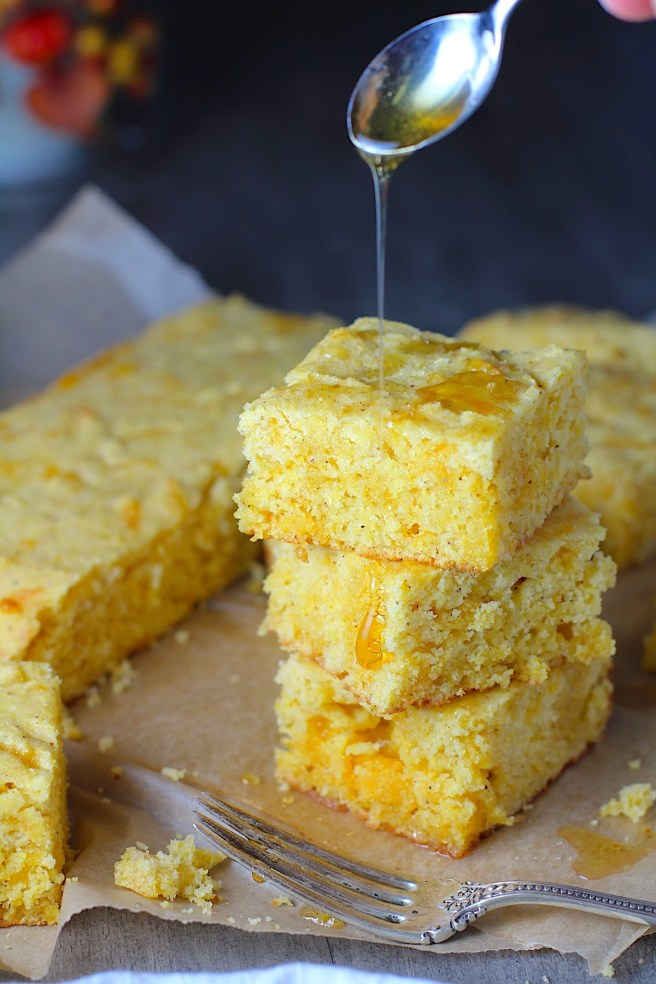 Cheddar Honey Gluten Free Cornbread pieces stacked on parchment paper with honey drizzled on top and fork and crumbs around.