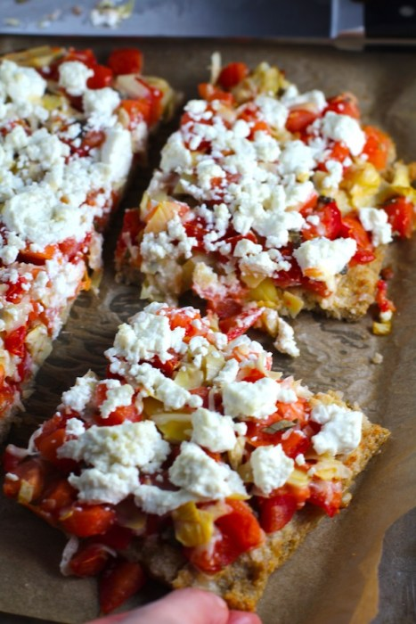 Close up of cut Tomato Tart on parchment. It gives you crunch from the Quinoa crust, a burst of fresh from the tomatoes, tons of flavor from the basil and garlic, tang and meatiness from the artichoke and so much creaminess from the mozzarella and goat cheese!  It's addictive and delicious!