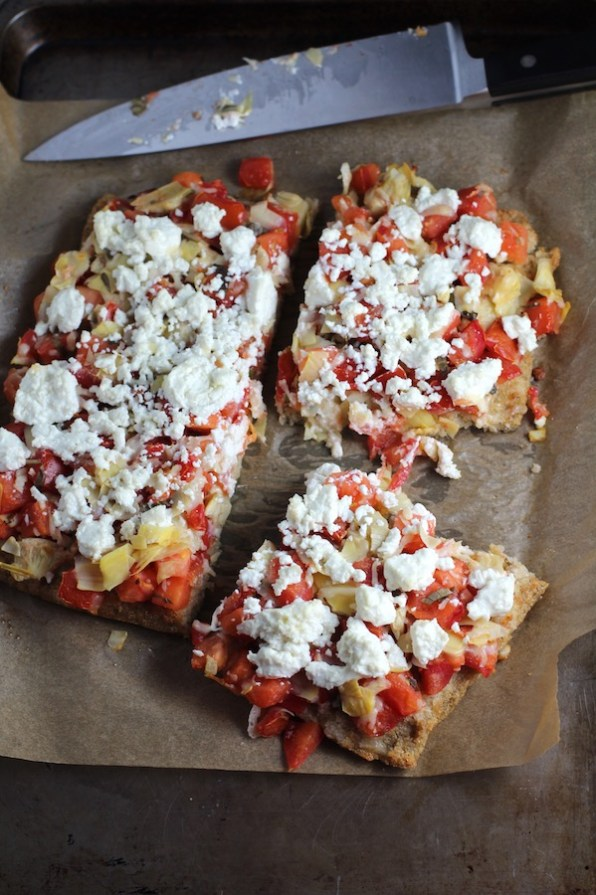 Square Tomato Tart cut into pieces on parchment. It gives you crunch from the Quinoa crust, a burst of fresh from the tomatoes, tons of flavor from the basil and garlic, tang and meatiness from the artichoke and so much creaminess from the mozzarella and goat cheese! It's addictive and delicious!