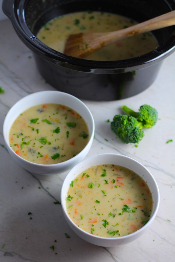 Slow Cooker Creamy Broccoli Soup in two boels on counter with crockpot in back.  This is easy, comforting, and delicious!  With Carrots, Broccoli, Onion, Garlic, and Oregano, this is one flavorful soup.  And, there is no heavy cream, just milk and a little half and half mixed with cornstarch, so it's healthy and gluten free!