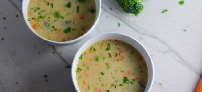 Slow Cooker Creamy Broccoli Soup in two bowls on counter with crockpot in back. This is easy, comforting, and delicious! With Carrots, Broccoli, Onion, Garlic, and Oregano, this is one flavorful soup. And, there is no heavy cream, just milk and a little half and half mixed with cornstarch, so it's healthy and gluten free!