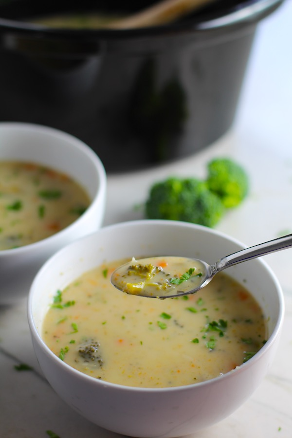 Light Slow Cooker Creamy Broccoli Soup in two bowls with spoonful on counter with crockpot in back. This is easy, comforting, and delicious! With Carrots, Broccoli, Onion, Garlic, and Oregano, this is one flavorful soup. And, there is no heavy cream, just milk and a little half and half mixed with cornstarch, so it's healthy and gluten free!