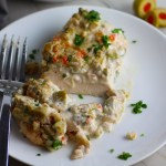 Creamy Olive Chicken cut on plate with fork. This is magnificently thick and creamy and infused with garlic flavor and nuttiness from the Parmesan. The best part; however, is the salty and briny flavor kick from the green olives with a little sweetness from the pimiento. #chicken #chickenrecipes #chickendinner #easydinners #easyrecipes #comfortfood #casserole