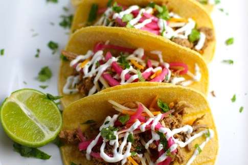 Slow Cooker Pork Tacos with with Pickled Onions, Shredded Cheese, and Cilantro Lime Crema drizzled on top! It's such an easy dinner since the pork cooks in the slow cooker to be perfectly seasoned and fall apart tender. #tacos #easydinner #glutenfree #dinner #mexican #pork