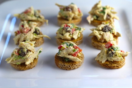Curry Chicken Salad on toast rouds on plate. It has so many fantastic flavors and textures!  The chicken breast is simply roasted and mixed with a creamy sweet and savory curry dressing.  Red pepper gives you a fresh crunch, scallion gives a savory bite, and raisins give a burst of sweet.  #chicken #chickenrecipes #chickensalad #currychicken #mealprep #lunch #healthyrecipes