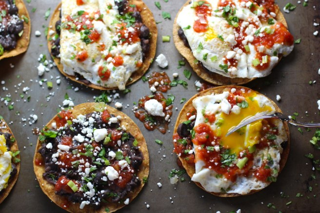 Huevos Tostadas assembled on a sheet pan are utterly delicious! They are similar to the better known Huevos Rancheros but are a pick up and eat with your hands version! They have crispy corn tortillas topped with creamy mashed black beans, a salty fried egg, smoky tomato sauce, cheese, and scallions! #huevosrancheros #eggs #brunch #mexicanrecipes #vegetarian #meatlessrecipes #glutenfree