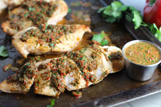 Chicken Chimichurri Rojo on a pan. It is roasted Chicken topped with a cool, fresh, tangy, and incredibly full-flavored! The Rojo comes from the addition of red pepper. All of the ingredients simply get blended in a food processor so it could not be easier! #chicken #chickenrecipes #chimichurri #easychicken #easydinners #dinner