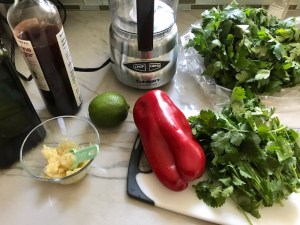 Ingredients on counter for the Chicken Chimichurri Rojo. It is broiled or grilled Chicken topped with a cool, fresh, tangy, and incredibly full-flavored! The Rojo comes from the addition of red pepper. All of the ingredients simply get blended in a food processor so it could not be easier! #chicken #chickenrecipes #chimichurri #easychicken #easydinners #dinner