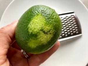 Zesting lime for Cilantro Lime Quinoa. It's fluffy, nutty, citrusy, salty, and the perfect accompaniment for any protein or vegetable! With just a few simple ingredients, you can make this fantastic healthier alternative to rice. #quinoa #quinoarecipes #sides #healthyfood