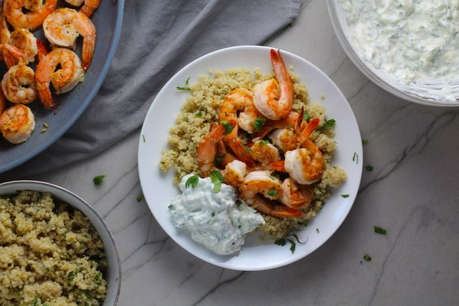 Garlic and Lime Shrimp with Tzatziki Sauce over Quinoa on plate. The Shrimp is simply sauteed with minced garlic, olive oil, and lemon for big bold flavors. The Tzatziki Sauce is bright and cool with creamy yogurt with fresh cucumber, lime, garlic, and scallion. #shrimp #easydinner #dinner #seafoodrecipes #shrimprecipes