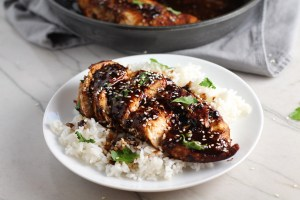 Sesame Sweet Chili Chicken cooked and sliced on a plate with rice and cilantro. It is slightly sweet, tangy, savory, nutty, with a touch of heat. You can prepare it days ahead, it takes just minutes to prepare, minutes to cook, and everyone will love it!! #chicken #marinades #easydinner #easychicken #chickenrecipes #easysauces #healthydinner #healthyfood #healthyrecipes