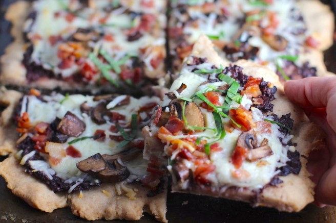 Hand holding a piece of Flatbread cut into 4 pieces on a pan with a crispy gluten free crust, salty and briny Olive Tapenade, creamy mozzarella, earthy and meaty mushrooms, peppery pancetta, and fresh basil. #flatbread #pizza #olives #tapenade #mediterranean #easydinner #dinner