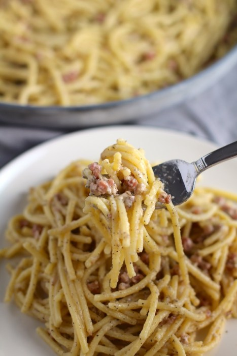 Pancetta, Parmesan, and Pepper Pasta on a plate and scooped up on a fork with pan in background. The Pancetta gives a salty and slightly peppery flavor, Parmesan cheese creates a nutty and creamy sauce, and the ground black pepper gives a peppery flavor that makes this pasta stand out. #pasta #easypasta #easydinner #dinner #italian #familydinner #onpotdinners #onepandinners #parmesan