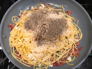 Pasta with Parmesan cheese and ground pepper on top in skillet for Pancetta, Parmesan, and Pepper Pasta. The Pancetta gives a salty and slightly peppery flavor, Parmesan cheese creates a nutty and creamy sauce, and the ground black pepper gives a peppery flavor that makes this pasta stand out. #pasta #easypasta #easydinner #dinner #italian #familydinner #onpotdinners #onepandinners #parmesan
