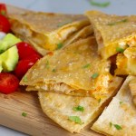 Chicken Corn Tortilla Quesadilla triangles on platter with avocado, tomato, & sour cream. They have crispy edges, a soft gooey center, and are mouthwatering flavor. They have hearty shredded chicken flavored with warm and smoky Mexican spices. Then shredded Pepper Jack cheese and Cheddar is layered to get melty and oozy and delicious. It's an irresistible new easy dinner or appetizer idea. #quesadillas #mexicanfood #enchiladas #familydinner #chicken