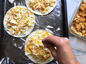 Hand sprinkling cheese on tortillas for Chicken Corn Tortilla Quesadillas. They have crispy edges, a soft gooey center, and are mouthwatering flavor. They have hearty shredded chicken flavored with warm and smoky Mexican spices. Then shredded Pepper Jack cheese and Cheddar is layered to get melty and oozy and delicious. It's an irresistible new easy dinner or appetizer idea. #quesadillas #mexicanfood #enchiladas #familydinner #chicken