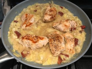 Chicken added to artichoke and sun dried tomatoes sauce in pan for Skillet Artichoke Chicken with sun dried tomatoes, basil, garlic, in cream sauce. #skilletchicken #skilletdinner #chicken #easydinner #familydinner #italian #tuscanchicken