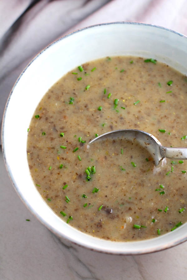 Thick & Creamy Mushroom Soup in a bowl with spoon filled with earthy mushrooms, aeromatic onions, flavorful oregano, and bright chives.