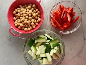 Chickpeas, sliced red pepper, and sliced zucchini for Chickpea Coconut Curry. The sauce has onion, coconut milk, ginger, garlic, and warm Indian Curry spices.