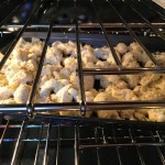 Coconut Cauliflower Bites baking in the oven. They have a slightly sweet and salty crunch outside from the shredded coconut and panko mixture.  The inside is soft and creamy.  Dip in the Sriracha Mayo.  Baked, not fried, so healthy!  Easy to make, easy to eat! #cauliflowerrecipes #healthyrecipes #sidedishes #appetizers #healthysnacks
