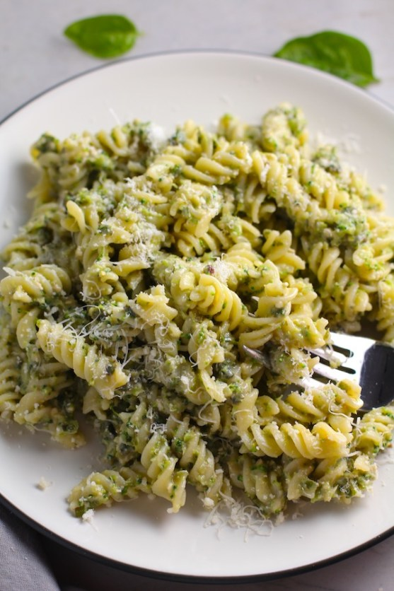 Broccoli Pesto Pasta on a plate with fork in pasta. It's delicious AND good for you!  It has all of the classic pesto flavors from garlic, basil, parmesan cheese, and pine nuts.  But the flavor is a bit more mellow by adding broccoli! #broccolirecipes #pesto #pasta #easydinner #dinnerideas #familydinner