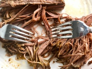 Forks shredding cooked brisket for Smoky Pulled Beef Brisket.  It's smokey, savory, tender, moist, and full of flavor. In a delicious sauce, it goes great on a sandwich, over polenta, on rice, or potatoes. #slowcooker #crockpot #brisket #beefbrisket #pulledbeef #pulledpork