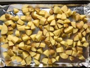 Cut potatoes on sheet pan for Patatas Bravas with chorizo and creamy Paprika aioli.  This Patatas Bravas Recipe, or Spicy Potatoes, is easy, indulgent, and utterly delicious! #potatorecipes #potatoes #potatosidedishes #patatasbravas #skilletpotatoes #sidedishes #chorizo