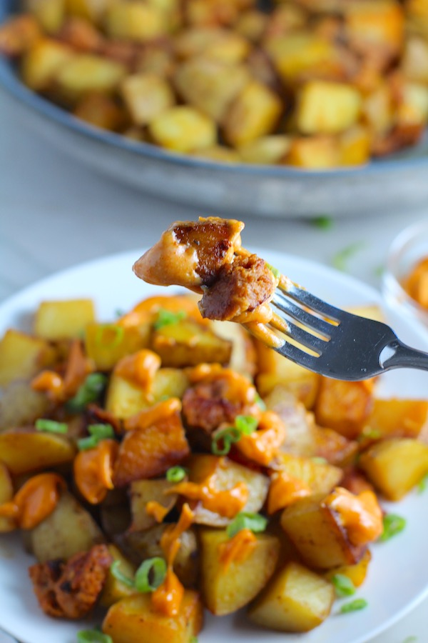 Bite of Patatas Bravas on a fork with more on a plate with chorizo and creamy Paprika aioli drizzled over top. This Patatas Bravas Recipe, or Spicy Potatoes, is easy, indulgent, and utterly delicious! #potatorecipes #potatoes #potatosidedishes #patatasbravas #skilletpotatoes #sidedishes #chorizo