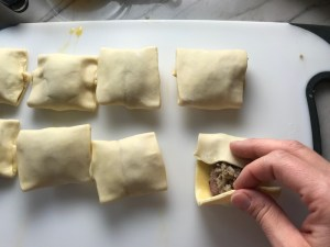 Hand folding puff pastry over filling for Mini Beef Wellington Bites. They are flaky and buttery Puff Pastry is filled with a creamy mushroom and parmesan filling and tender beef filet.  #appetizers #partyfood