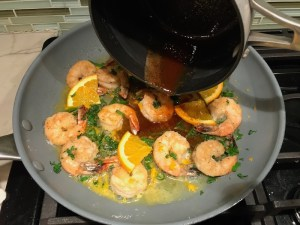 Adding brown butter to shrimp in skillet for the Orange Brown Butter Shrimp Pasta Recipe. #shrimprecipes #shrimppasta #easydinners #dinnerideas