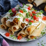 Baked Chicken Taquitos stacked on plate with toppings. Corn tortillas are filled with smoky taco seasoned shredded chicken, and creamy cheddar cheese.  #dinnerideas #familydinner #chickenrecipes #chickendinner #tacos #taquitos