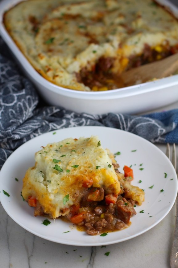 Piece of Cottage Pie on plate with dish in back. This recipe has Spanish Chorizo and ground beef cooked in a rich and savory gravy with veggies and herbs.  Creamy mashed potatoes sit on top with manchego, parmesan, and garlic. #dinnerideas #cottagepie #shepherdspie