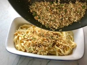 Pouring cracker crumbs over pasta for Bacon Mac and Cheese. It has a creamy and cheesy sauce with a touch of smokiness from the bacon, coats each piece of pasta.  On top, crispy crunchy, indulgent bacon fat cracker crumbs!