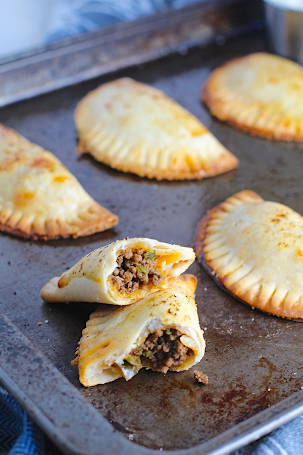 Ground Beef Empanadas on a pan.  Flaky, buttery pastry on the outside with a savory, smokey, salty ground beef filling.